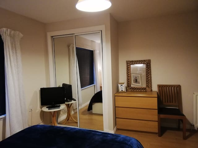 Spacious double bedroom 1 with mirrored wardrobe, bedside cabinet, chest of drawers, TV and a small sofa.