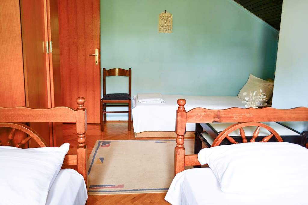 The room features three single beds.