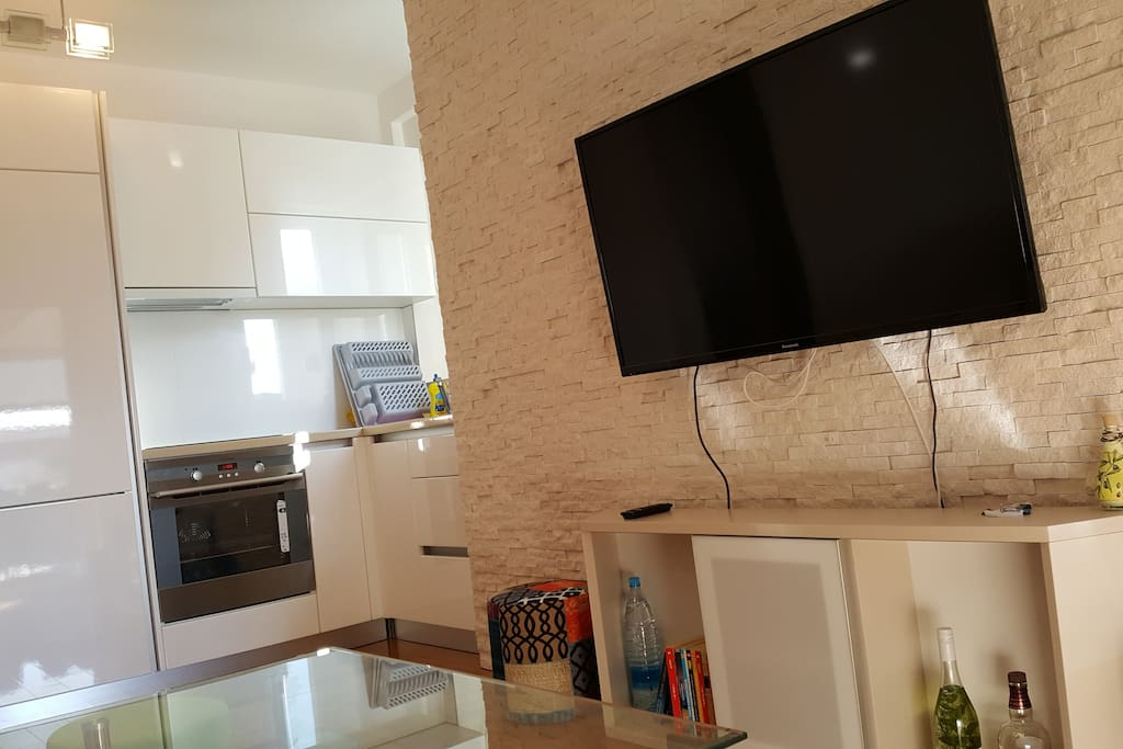 Living room with tv, sofa for tv and fully equipped kitchen.