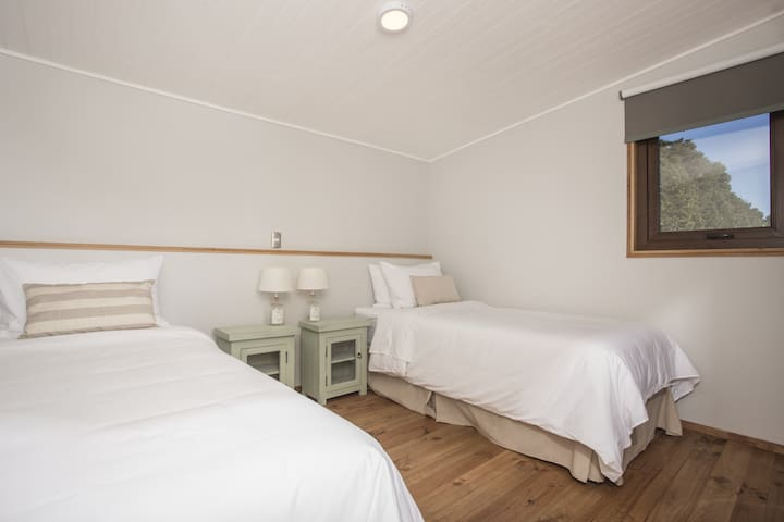 Secondary bedroom features two single beds, which can be joined to form a king-size bed. Also fitted with closets, blackout curtains, and indirect lighting.