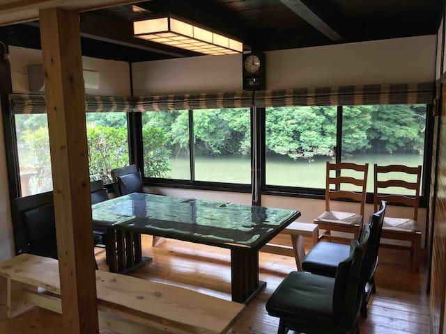 広いダイニングと手作りの大きな一枚板のベンチ。 目の前の川をゆったりと眺めるのに最適です。