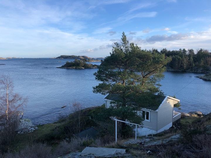 Hytte med privat strandlinje og båt