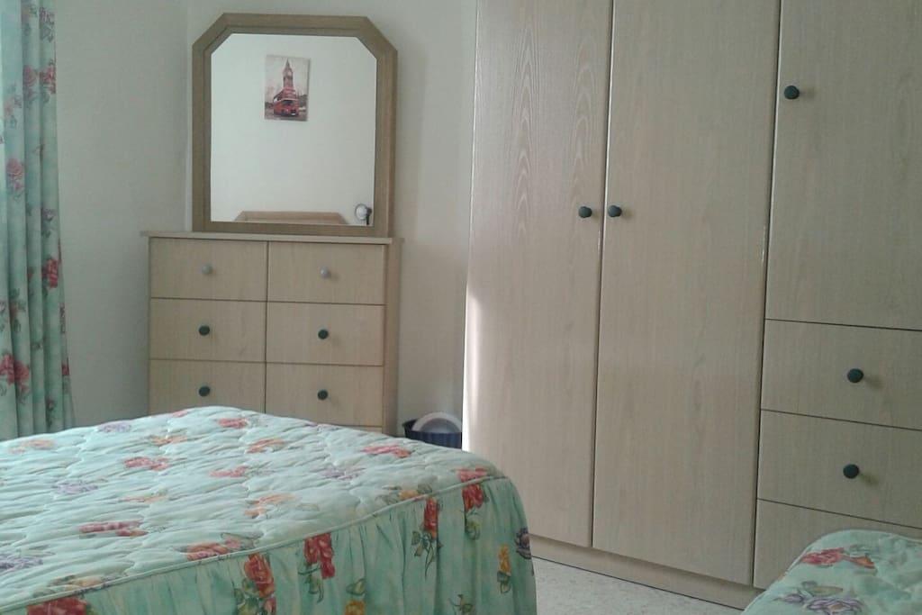 Dormitorio doble,  camas individuales, mesilla, armario y cajonera con espejo. Muy luminoso.