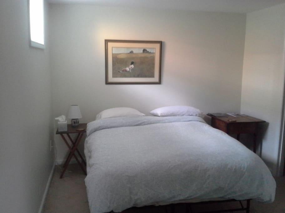 Comfortable queen bed with pillow top mattress in clean, sunny bedroom.