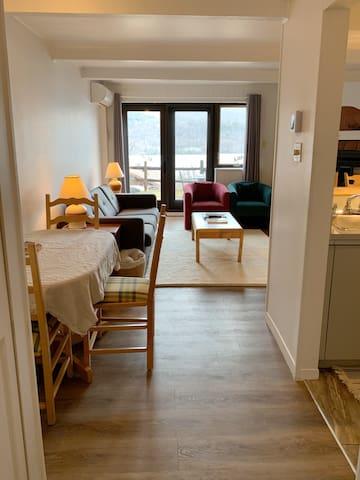 View from the entryway. Dining area, living room with sofa bed, fireplace and access to the outdoor terrace.   Vue de l'entrée du condo. Espace pour manger, salon avec divan-lit, foyer et accès à la terrasse extérieure.