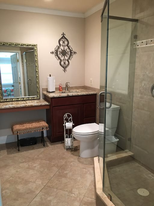 Full bath with closet for hanging and drawers, granite counter top, and a makeup counter.