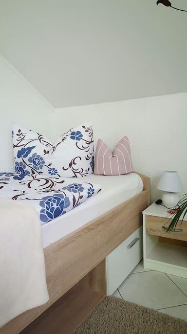 Einzelbett mit Kuscheldecke und Handtüchern