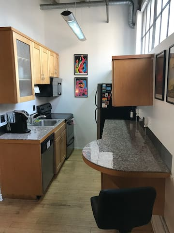 Modern kitchen with microwave oven, stove, full-size refrigerator, and dining counter.