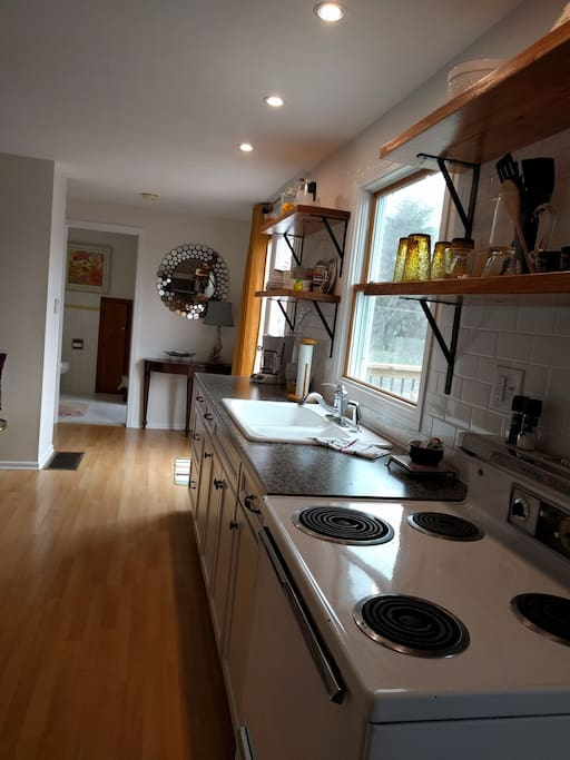 Kitchen, sink area, coffee maker with coffee and cream, electric original stove! still works great, refrigerator, microwave,open shelving