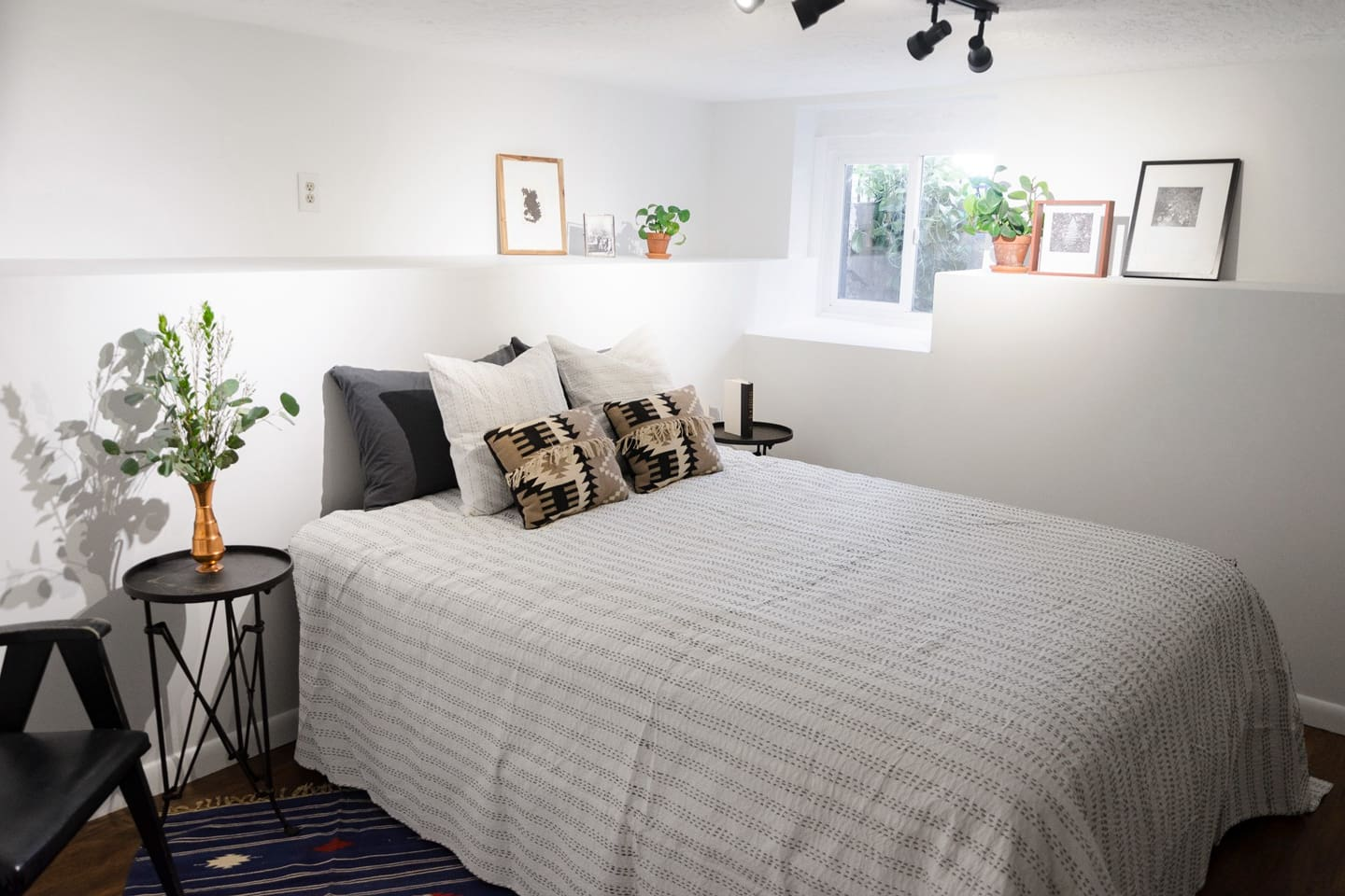 The bedroom has a queen size bed, plenty of closet space and shelving, and a window to the backyard.