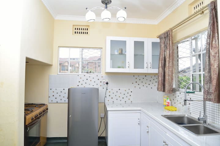 Kitchen with fridge, cooker and microwave