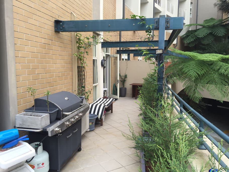 The large balcony/terrace (backing directly onto the train line) has a barbecue and two table settings. And lots of plants, too!