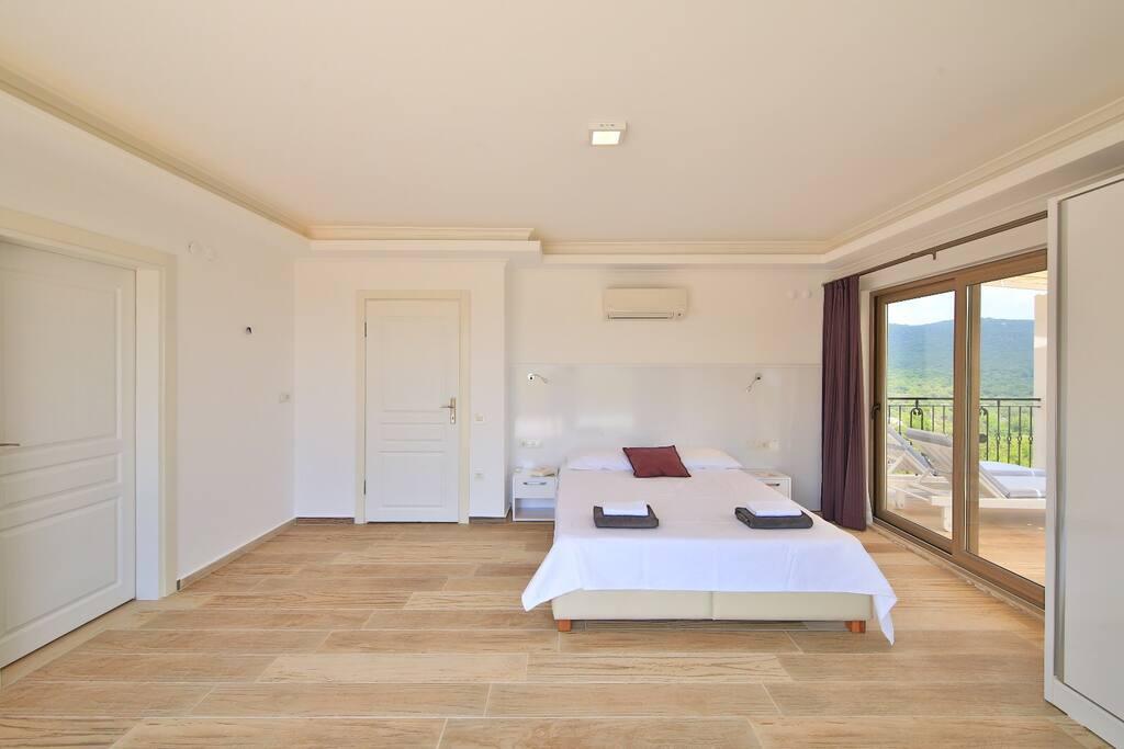 Slaapkamer 1 met dubbel bed, eigen terras met ligbedden en prachtig uitzicht