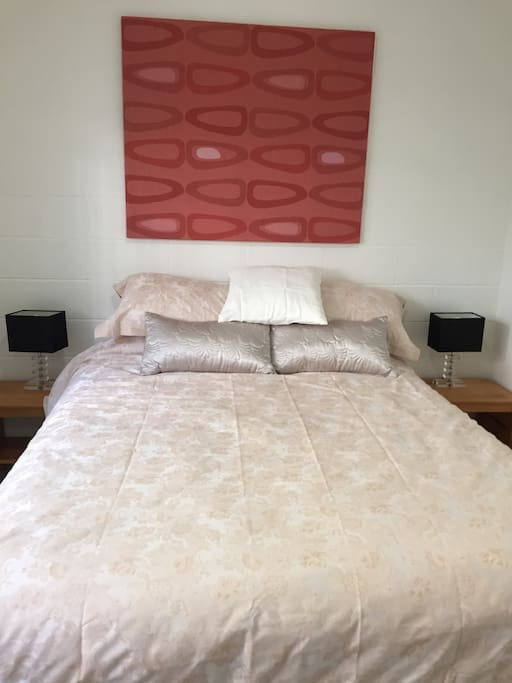 Main bedroom queen bed,  built in wardrobe and garden views