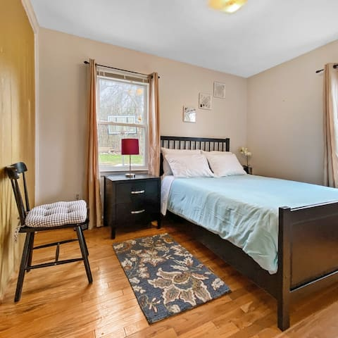 The second light filled bedroom offers guests a comfortable queen bed and separate seating area