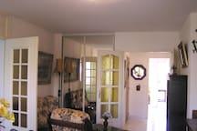 Vue du séjour vers le hall d'entrée et le couloir d'accès aux chambres louées