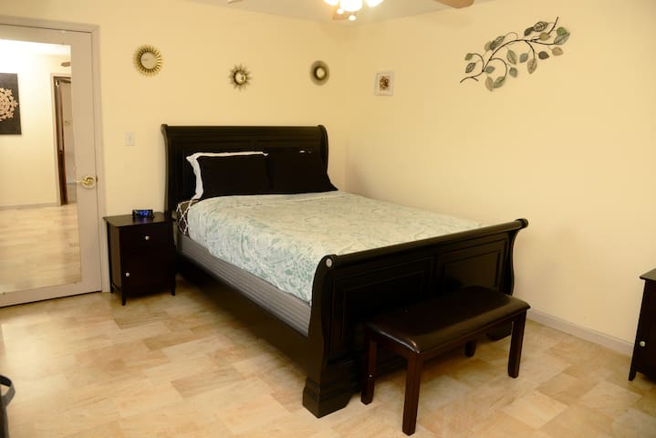 Master bedroom, queen bed, smart tv,  with walk in closet and window with view of the lake.