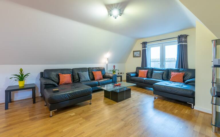 The living room has two large chaise-end leather sofas where you can put your feet up to relax.