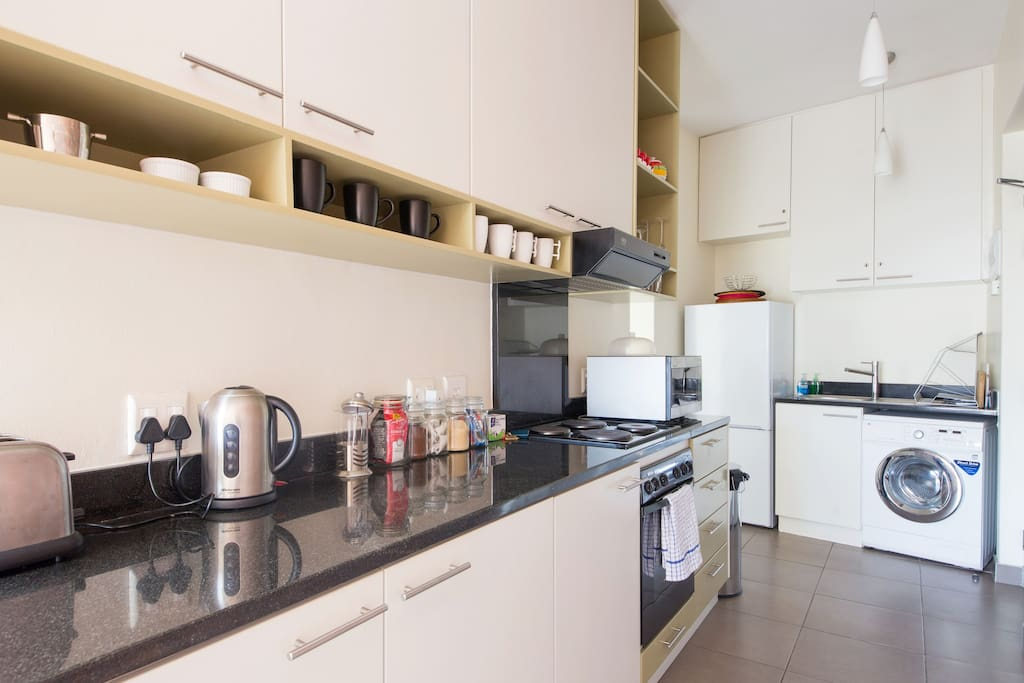 Fully-equipped kitchen with all appliances including washing machine.
