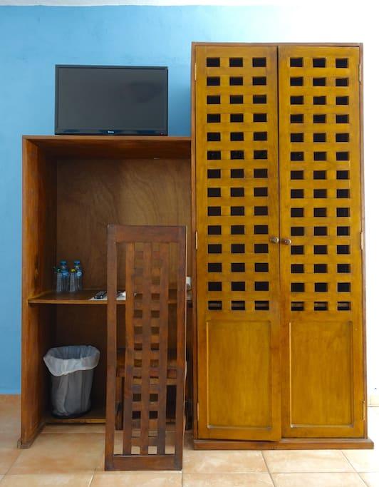 Closet, desk, and TV in room