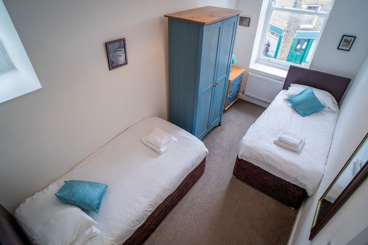 Bedroom 4 has 2 single beds. Views are over High Street towards Kinder Scout