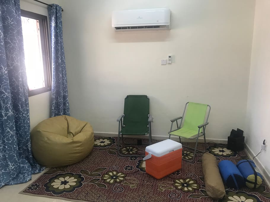 Sitting area with the camping gear that is provided for camping trips during your period of stay: cool box, chairs, tent, mattress and sleeping bags
