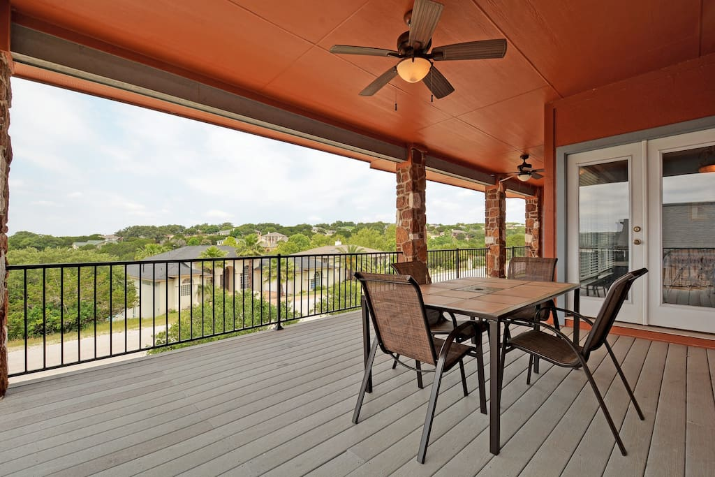 A second story deck with outdoor seating overlooking the lake.