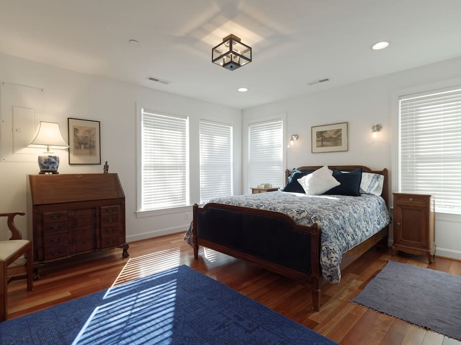 Master bedroom with queen bed, slant front antique desk, chair and double closets