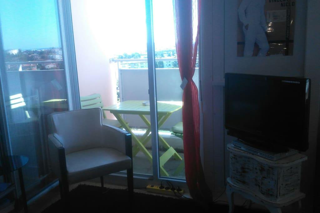 fauteuil et TV dans la chambre privatif avec table et chaises sur le balcon vue sur Toulouse.