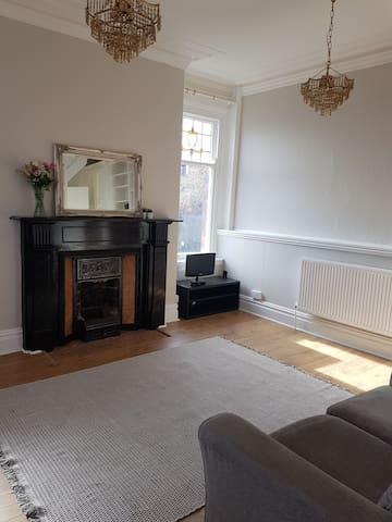 Victorian sitting room with beautiful fire place and windows to the front and side.