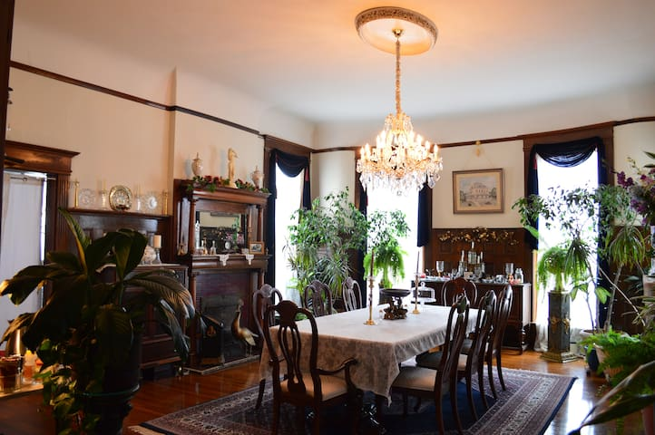 The Formal Dining Room. Done in walnut with beautifully carved fireplace mantle and wainscot. Graced by an incredible Maria Theresa Crystal Chandelier with hand polished Austrian crystal.