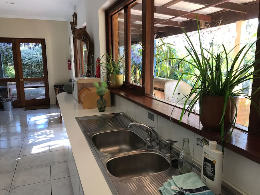 Enjoy preparing meals in the spacious kitchen while looking out over the bush and garden