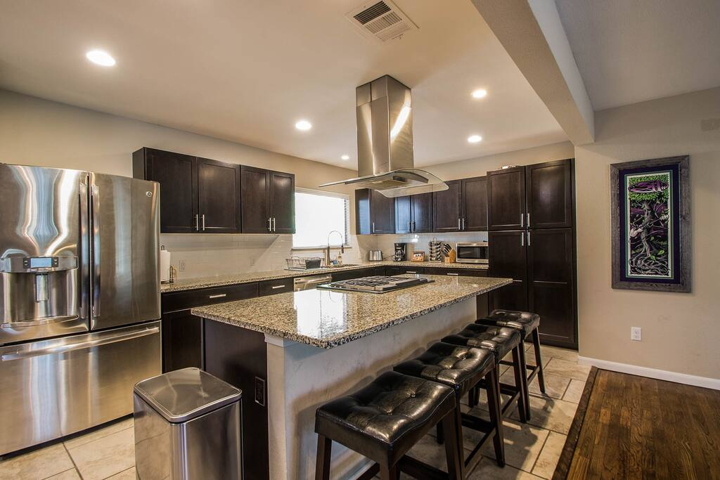 Large open kitchen with modern appliances. Stocked with utensils and spices/herbs.