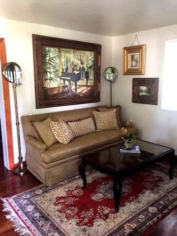 Comfortable living room with silk rug, Hardin sofa, oil paintings, glass protected designer coffee table, and 2 dimmable floor lamps.