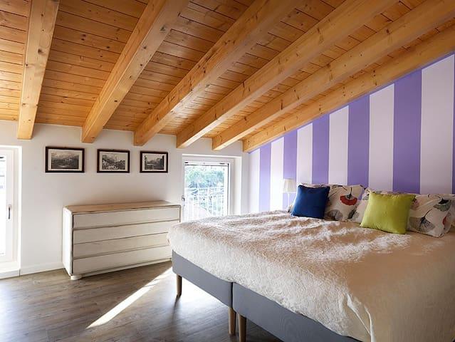 Camera con vista sui tetti del centro, finestre con zanzariere e ante regolabili.