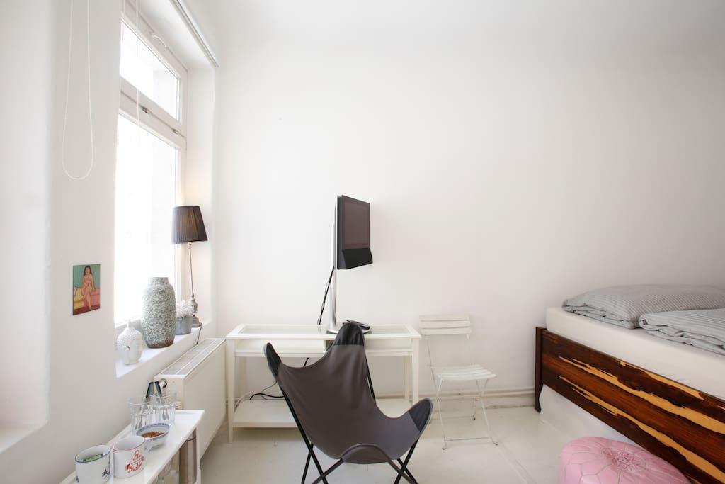 Schlafzimmer mit Sessel und Fernseher