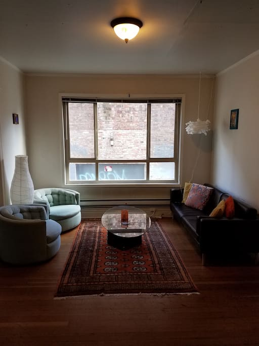 Enjoy a large living room with big open windows, hardwood floor and interesting touches.