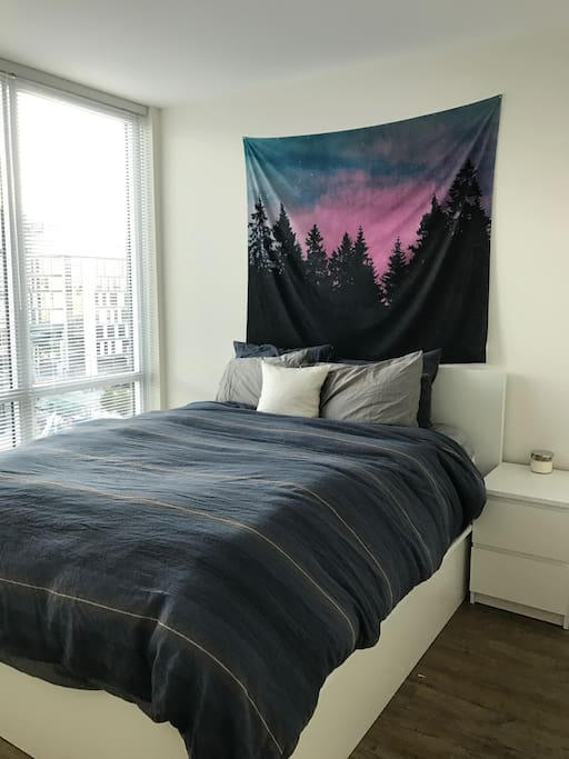 Bedroom with queen bed and full wall of windows.