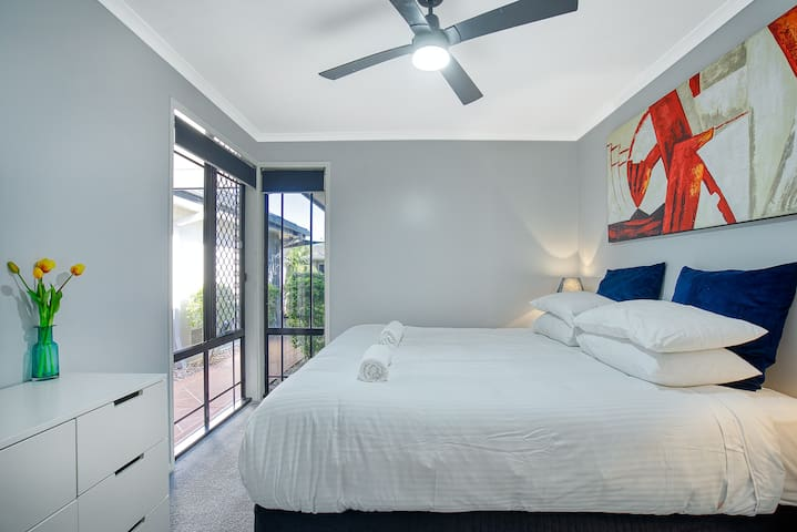 A second bedroom also comes furnished with a king bed and has a chest of drawers and a ceiling fan.