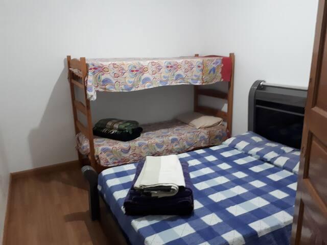 Quarto com cama de casal e beliche.