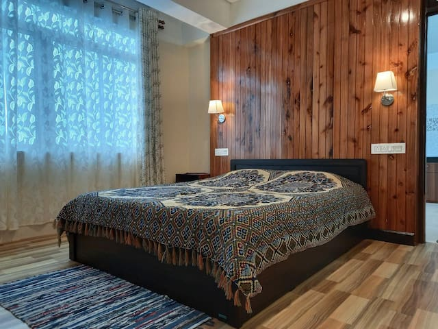The Master Bedroom is spacious & has an ensuite bathroom. The wooden panelling adds warmth to the space & makes it cosy. The windows overlook the view of the valleys and tea gardens.
