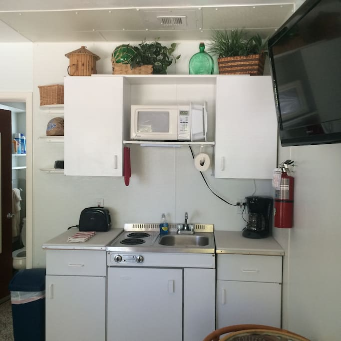 Small kitchen, two burners, microwave, dishes. Gas BBQ grill outside