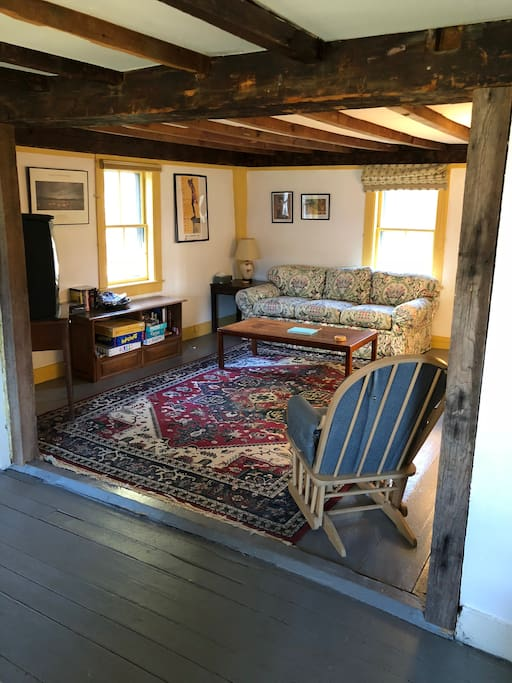 Living room, with monitor/TV on left, exposed beams, and large comfortable space