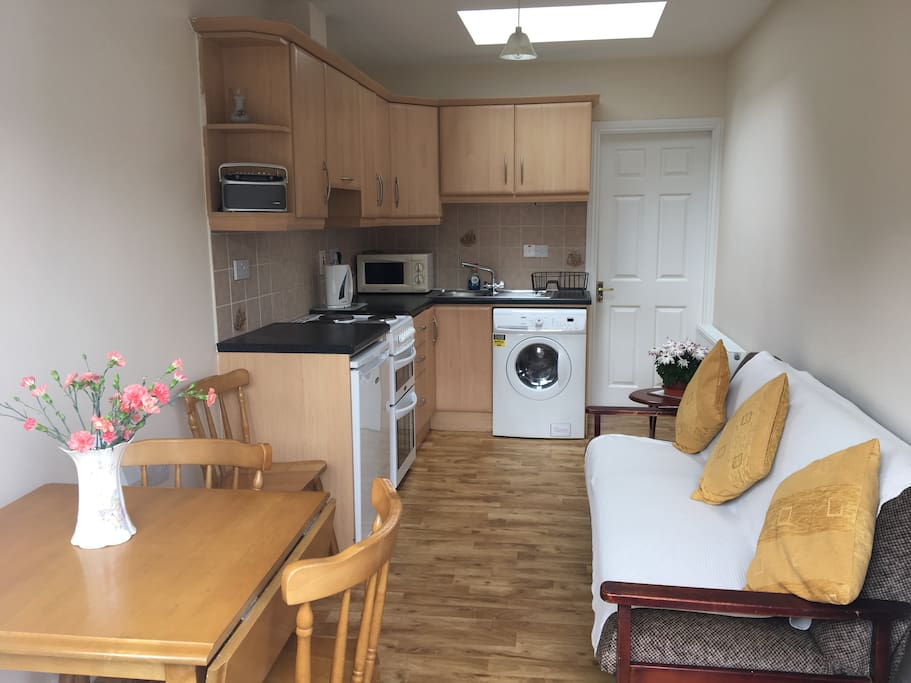 Kitchen with washing machine & dryer, sofa, table and three chairs.