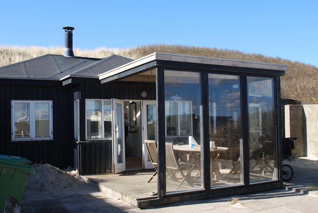 Huset udefra med havet og stranden lige på den anden side af klitten