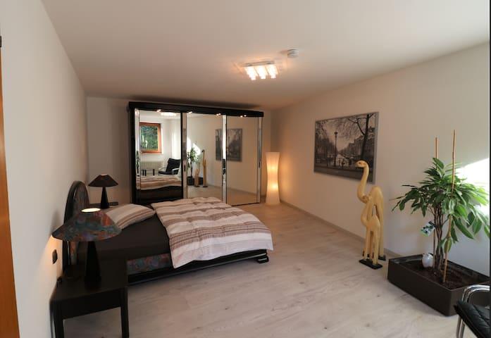 Schlafzimmer mit großem beleuchtetem Schrank und komfortablem Doppelbett 160m Breite