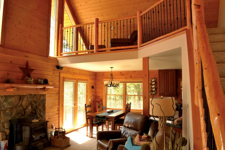 Main living area and loft with comfortable leather furniture, fireplace, ceiling fan, and view of the Sangre de Cristo Mt. Range and the pine forest surrounding the cabin.