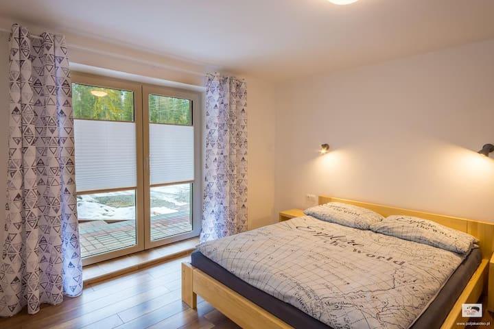 Klimatyczna sypialnia z dużym, dwuosobowym łóżkiem i wyjściem na taras