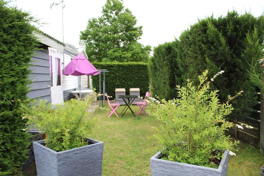 Une partie du jardin avec coin repas + plancha + bains de soleil
