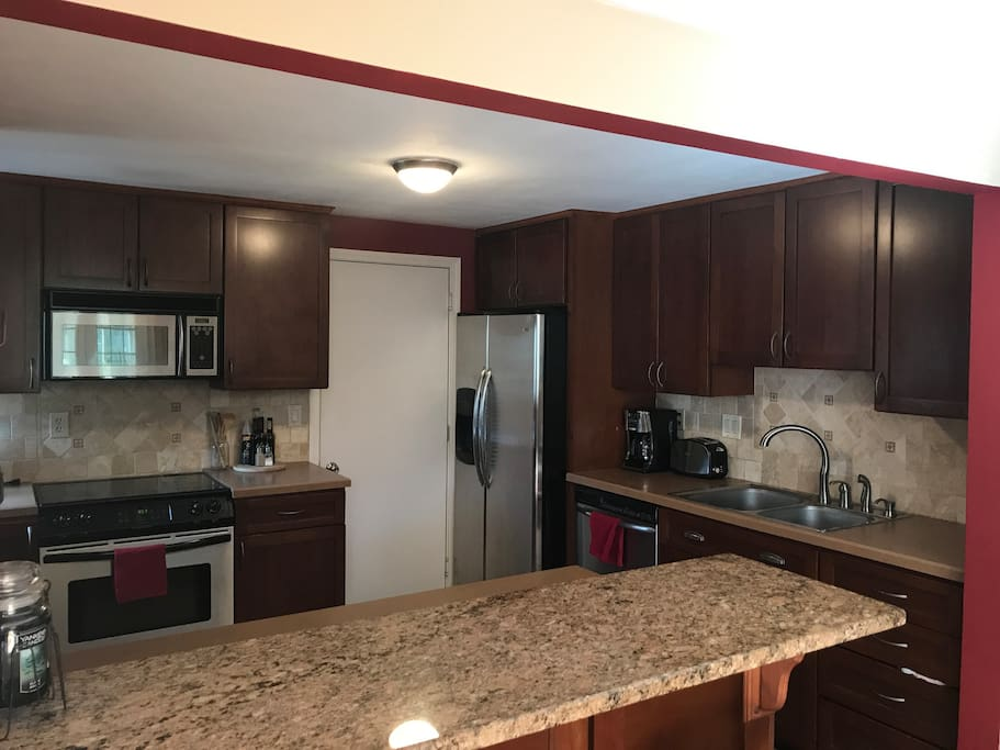 Kitchen with stainless steel appliances & breakfast bar